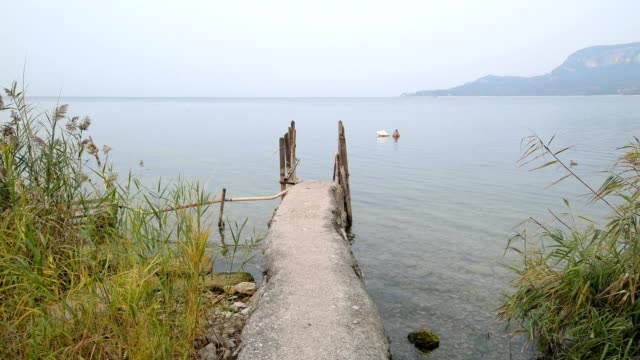 lake garda with stone jetty in the morning, garda, lake garda, lago di garda, veneto, italy - lago stock videos & royalty-free footage