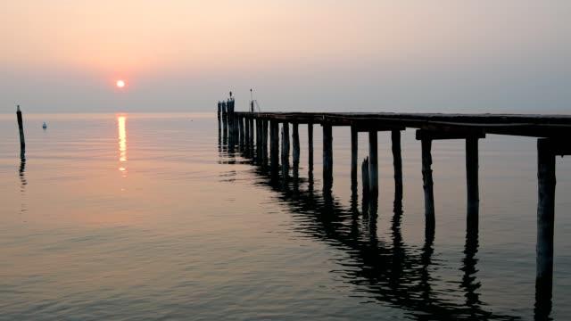 lake garda with wooden jetty at sunset, lazise, verona, lake garda, lago di garda, veneto, italy - lago stock videos & royalty-free footage