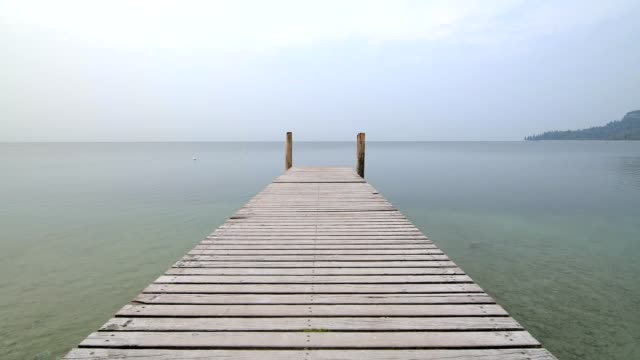 lake garda with wooden jetty in the morning, garda, lake garda, lago di garda, veneto, italy - lago stock videos & royalty-free footage