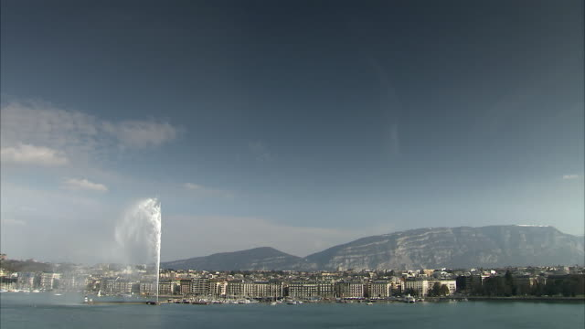 ws of lake geneva and the famous fountain, jet d'eau with skyline and saleve mountain / geneva, switzerland - lake geneva stock videos & royalty-free footage