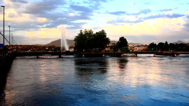 Genfer Fontäne im Genfer See und den Sonnenuntergang von Alpen