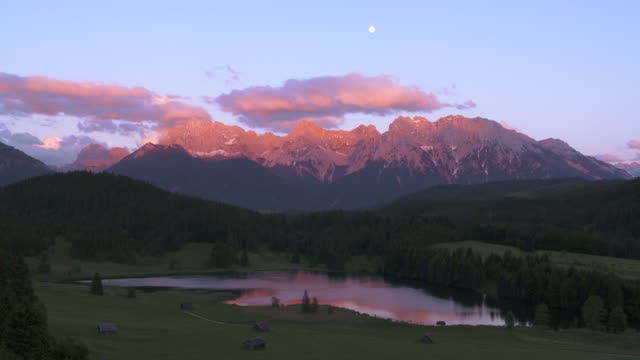 vídeos de stock, filmes e b-roll de lake geroldsee with huts and karwendel mountains in background at full moon, sunset. - garmisch partenkirchen