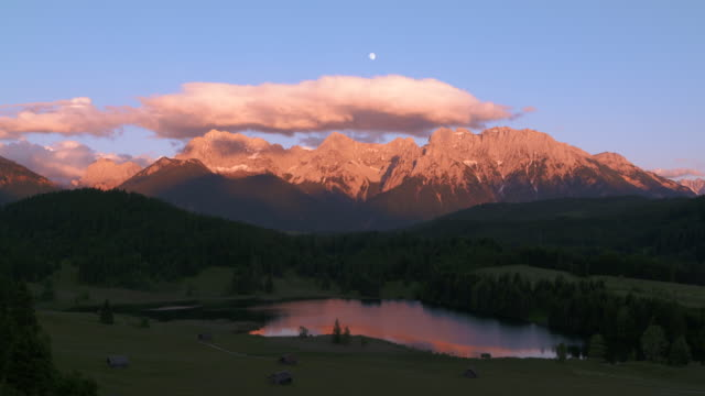 lake geroldsee with huts and karwendel mountains in background at full moon, sunset. - karwendel mountains stock videos and b-roll footage