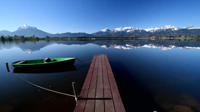 lake hope with wooden jetty and rowboat, hopfen am see, allgau, bavaria, germany - jetty stock videos & royalty-free footage