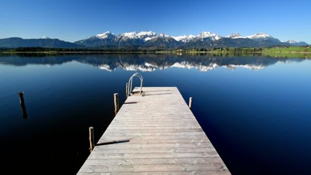 lake hope with wooden jetty, hopfen am see, allgau, bavaria, germany - ruhige szene stock-videos und b-roll-filmmaterial