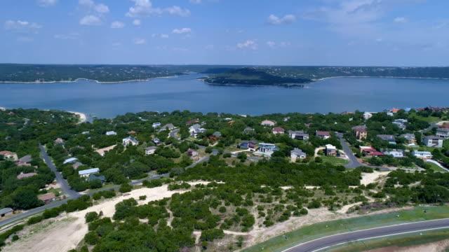 stockvideo's en b-roll-footage met meerhuis voorstad op lake travis buiten austin, texas luchtfoto drone weergave boven wijk uitje water front eigenschap met road in beeld - sunshine lake