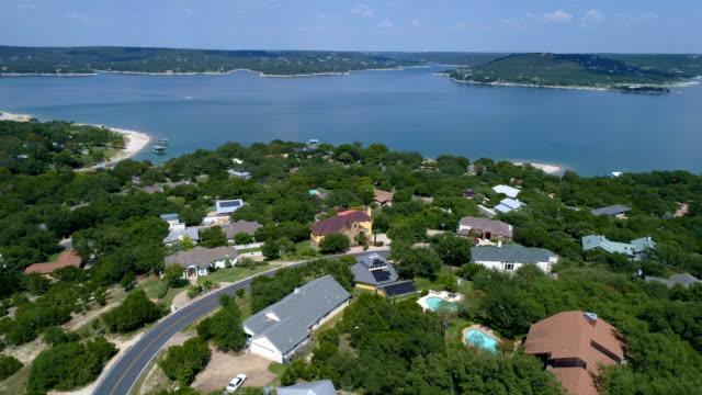 stockvideo's en b-roll-footage met meerhuis voorstad op lake travis buiten austin, texas luchtfoto drone weergave boven wijk uitje - sunshine lake