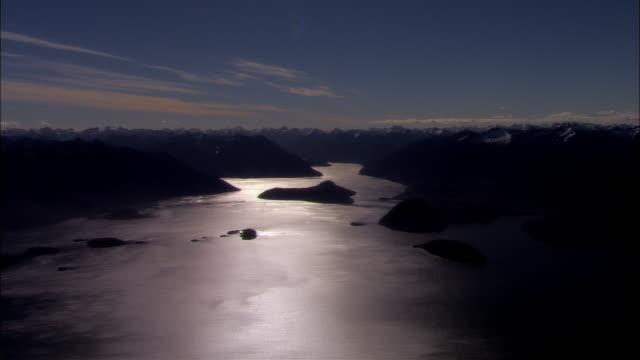 low aerial, lake manapouri, fiordland national park, new zealand - viraggio monocromo video stock e b–roll