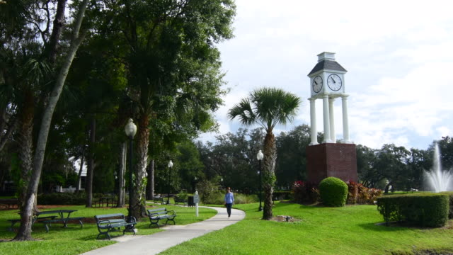 lake mary florida downtown woman walking in park central park at clock tower in new shopping center park, 4k - turmuhr stock-videos und b-roll-filmmaterial