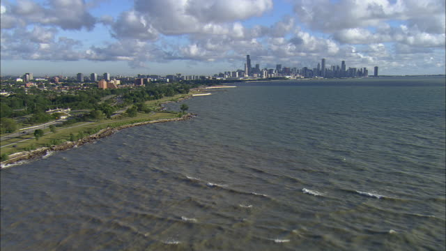 low aerial, lake michigan with city skyline in distance, chicago, illinois, usa - distant stock videos and b-roll footage