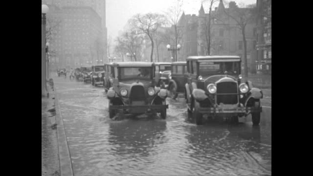 lake michigan's waves crash over a seawall / model a cars driving in high water on a street / a man walks along the seawall with others at a wrecked... - lake michigan stock videos & royalty-free footage