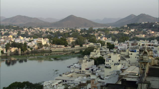 HA WS PAN Lake Pichola and buildings in cityscape with mountains in background / Udaipur, India
