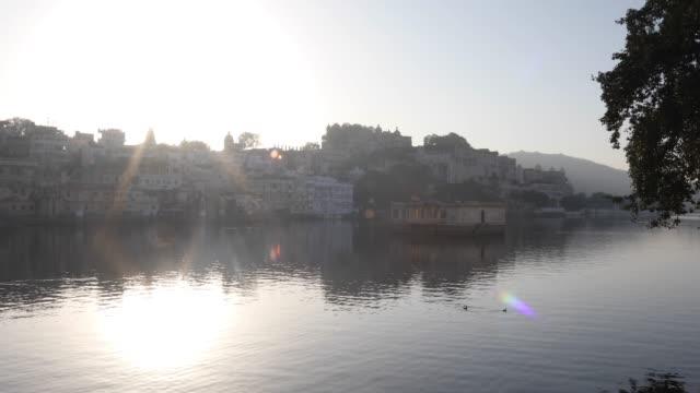 Lake Pichola and distant city palace at sunrise