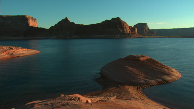 ms, lake powell and rock formations at dusk, glen canyon national recreation area, utah, usa - lago powell video stock e b–roll