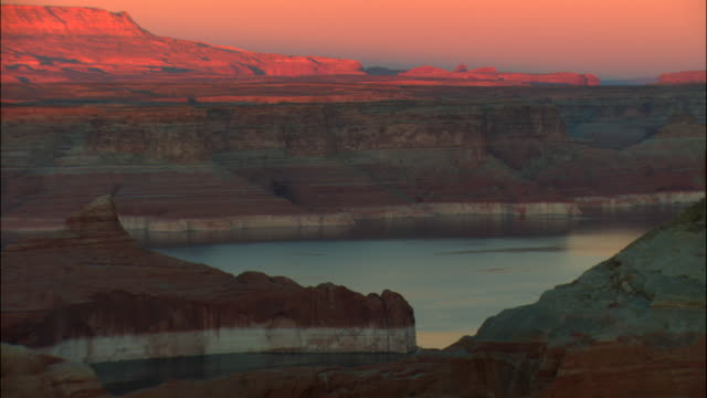 vídeos de stock e filmes b-roll de ms, ha, lake powell and rock formations at sunset, glen canyon national recreation area, utah, usa - lago powell