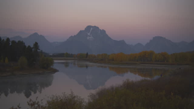 a lake reflects the image of a rocky mountain in grand teton national park. - grand teton national park stock videos & royalty-free footage
