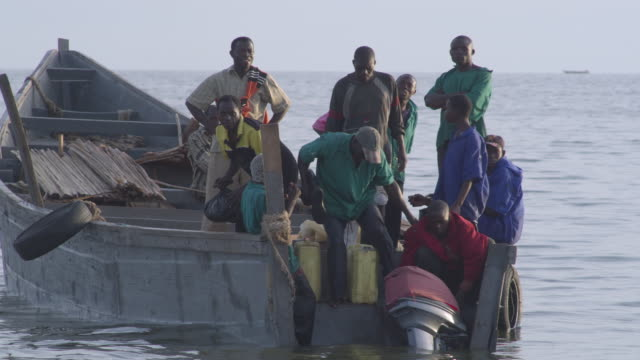 ws td tu lake shore small passenger boat children playing by water / buikwe, uganda - 腰に手を当てる点の映像素材/bロール