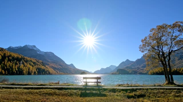 lake silsersee with bench and sun in autumn, sils im engadin, engadin, grisons, switzerland, european alps - sunny stock videos & royalty-free footage