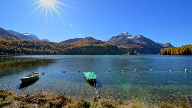 lake silsersee with boat and sun in autumn, sils im engadin, engadin, grisons, switzerland, european alps - viewpoint stock videos & royalty-free footage