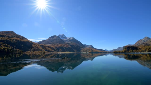 lake silsersee with canoe and sun in autumn, sils im engadin, engadin, grisons, switzerland, european alps - alps stock videos and b-roll footage