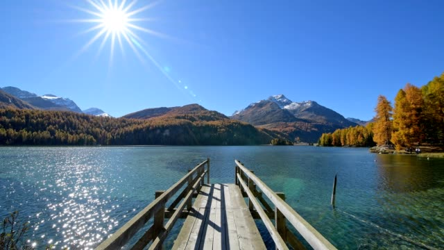 lake silsersee with wooden jetty and sun in autumn, sils im engadin, engadin, grisons, switzerland, european alps - alps stock videos and b-roll footage