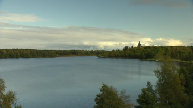 ws lake surrounded by trees, castle in distance / vaxjo, sweden - vaxjo stock videos & royalty-free footage