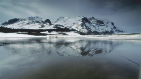 t/l ws pan lake surrounded with snowcapped mountains, banff national park, alberta, canada - panning stock videos & royalty-free footage