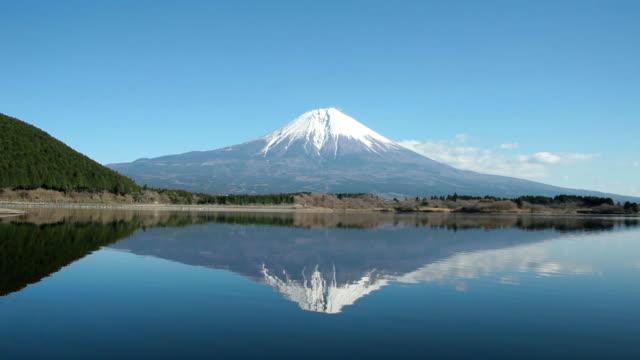 lake tanuki reflects snowy mt. fuji in shizuoka, japan. - shizuoka prefecture stock videos and b-roll footage