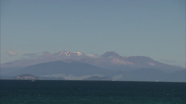 lake taupo with mount ruapehu visible with a few streaks of snow seen across water and conical peak of mount ngauruhoe visible to the right - ngauruhoe stock videos & royalty-free footage
