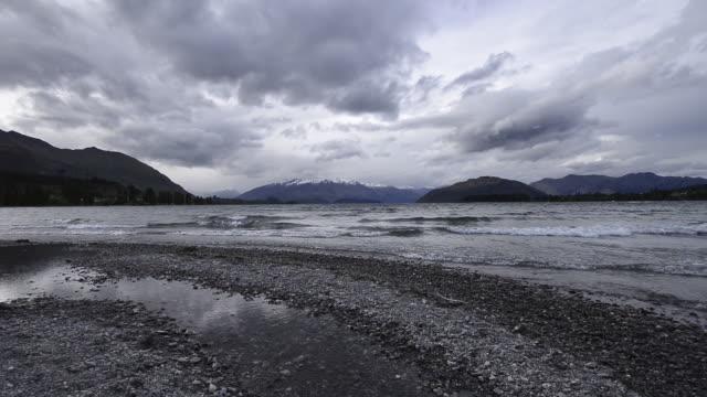 lake wanaka with snowcapped mountains in background and dramatic cloud sky. wanaka, lake wanaka, otago region, south island, new zealand, australasia. - otago region stock videos & royalty-free footage