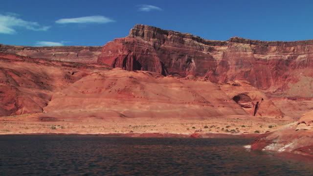 vídeos de stock e filmes b-roll de lake water ripples against a red sandstone plateau. - arenito