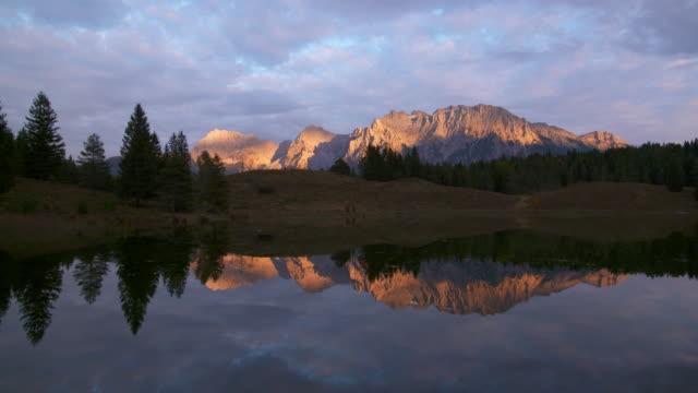 lake wildensee at sunset, karwendel mountains in background. mittenwald, garmisch-partenkirchen, wildensee, karwendel, werdenfelser land, upper bavaria, bavarian alps, bavaria, germany, europe. - karwendel mountains stock videos and b-roll footage