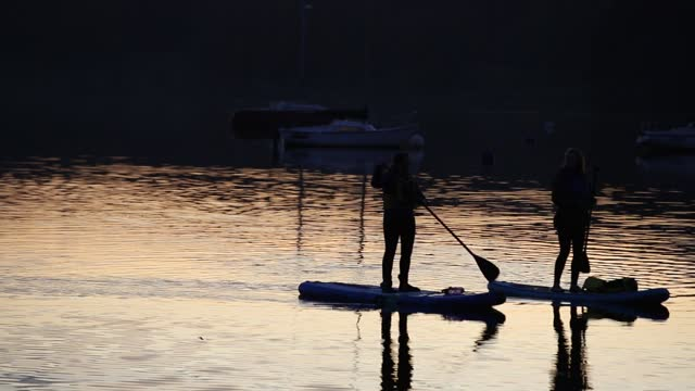 lake windermere at sunset, ambleside, lake district, uk with women paddle boarding. - oar stock videos & royalty-free footage