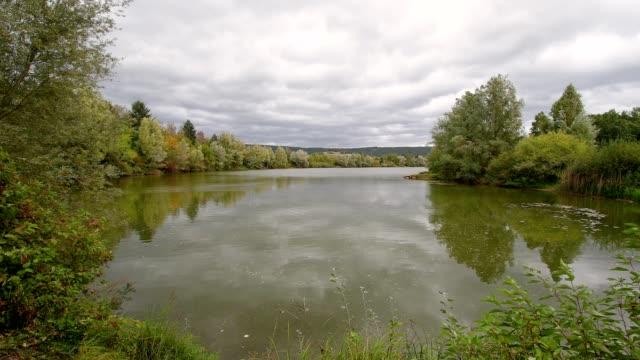 Lake with cloudy sky on windy autumn day, Mondfeld, Wertheim, Main-Tauber-Kreis, Baden-Württemberg, Germany