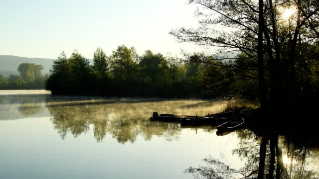 lake with morning haze and sun in spring, freudenberg, baden-wurttemberg, germany - 湖点の映像素材/bロール