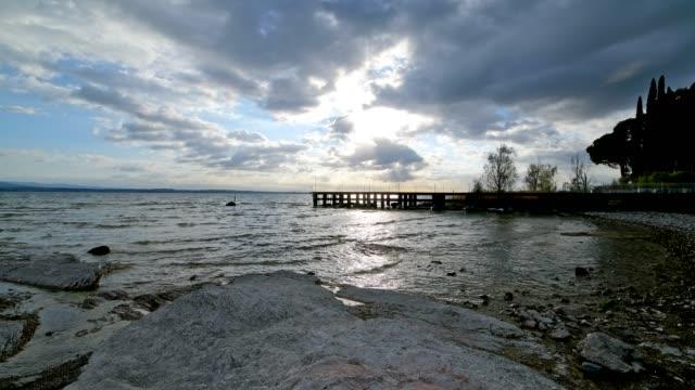 lake with pier in the morning, sirmione, brescia, lake garda, lago di garda, lombardy, lombardei, italy - lago stock videos & royalty-free footage