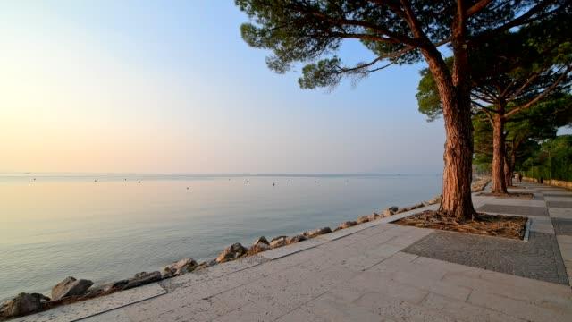 lakeshore at sunset, lazise, verona, lake garda, lago di garda, veneto, italy - lago stock videos & royalty-free footage