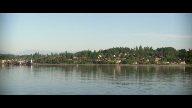 ws pan pov lakeshore with houses amid hills - lakeshore stock videos & royalty-free footage