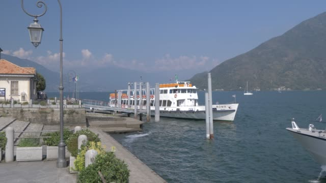 lakeside walk and ferryboat leaving harbour in cannobio on lake maggiore, lake maggiore, piedmont, italian lakes, italy, europe - ferry stock videos & royalty-free footage
