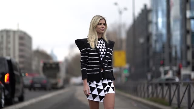 vídeos y material grabado en eventos de stock de lala rudge wears a black and white striped jacket with shoulder pads, a balck and white dress with printed triangles, black shiny pvc boots, outside... - vestimenta para mujer