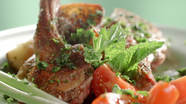 cu lamb chops on dinner plate with fried potatoes, tomatoes and basil as parsley is sprinkled over rotating plate - mint leaf culinary stock videos and b-roll footage