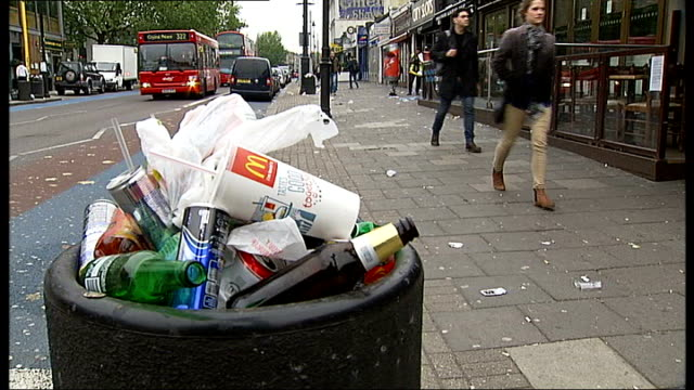 lambeth council leaves one half of street uncleaned to highlight littering problem; england: london: clapham high street: ext rubbish strewn across... - itv london tonight weekend stock videos & royalty-free footage