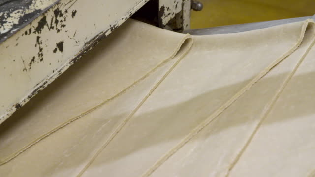 laminated dough rolls through machinery - cracker stock videos & royalty-free footage