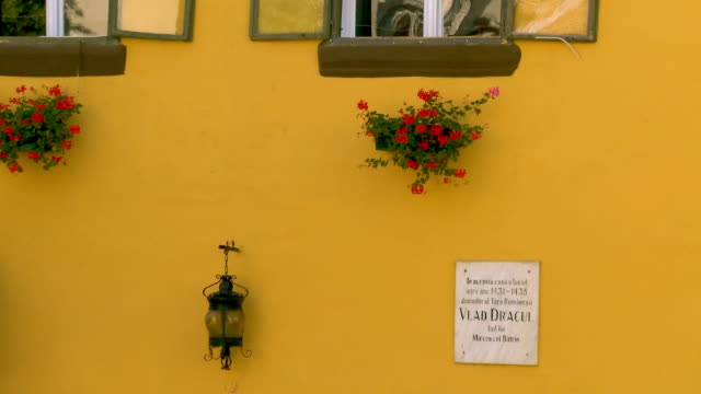 ms zo lamp and flowerpot hanging on yellow wall /sighisoara, romania - sighisoara stock videos & royalty-free footage