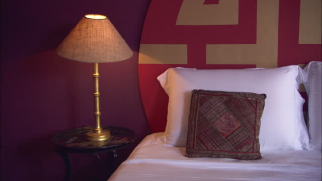 A lamp glows on a nightstand in a La Maison Hotel room in Rio de Janeiro.