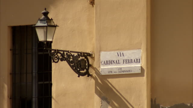 a lamp post and street sign on the wall of the parma cathedral. available in hd. - parmigiano video stock e b–roll