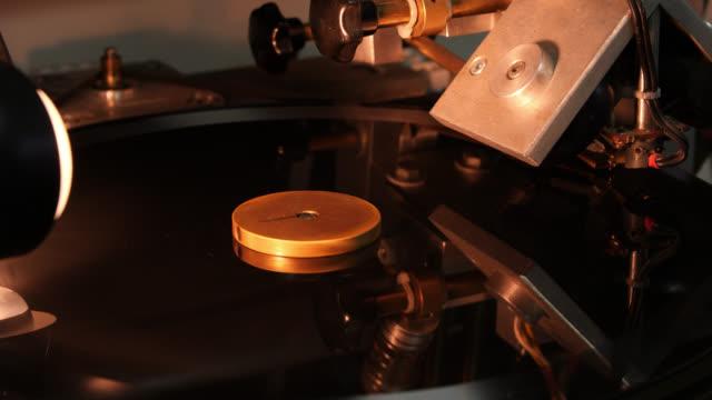 vídeos de stock e filmes b-roll de a lamp shines on a rotating black vinyl disc - gira disco