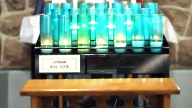 vídeos y material grabado en eventos de stock de lampions lit in a church - figura femenina