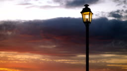 Lamppost. A light at the top of a tall post in the street against the red sky. 4K