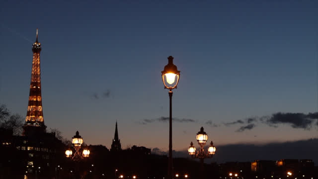 lamppost of the alexandre iii bridge and the illuminated eiffel tower during the 6pm curfew, to help stop the spread of the coronavirus , on march... - electric lamp stock videos & royalty-free footage